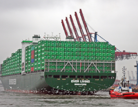 A gigantic fully loaded Evergreen freight shipping company boat.