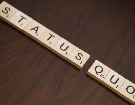 Scrabble tiles laid out to spell 'Status-Quo'